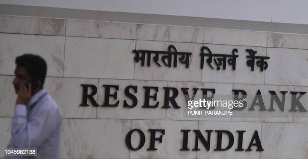 An Indian man speaks on the phone outside the Reserve Bank of India head office in Mumbai on October 5 2018 India's rupee breached 74mark to the...