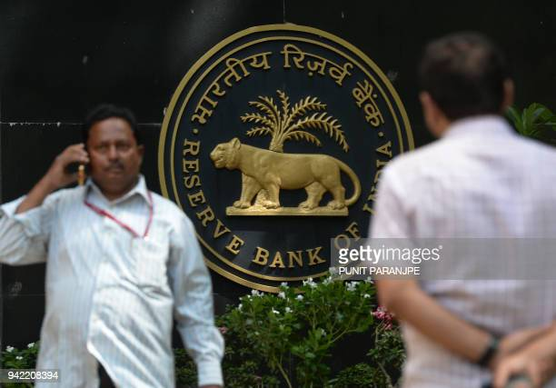 An Indian man speaks on the phone outside the Reserve Bank of India head office in Mumbai on April 5 2018 India's central bank on April 5 kept...