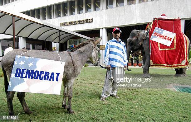 An Indian man stands between a donkey bearing a Democrats banner and an elephant bearing a Republicans banner during an election watch organised at...