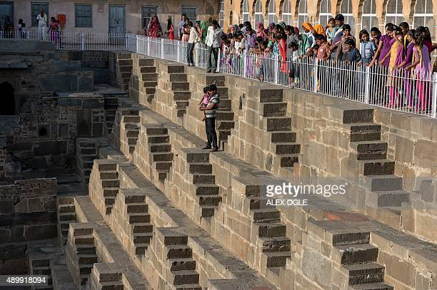 An Indian man stands with his child as others look on at the historic Chand Baori stepwell in Abhaneri village in Rajasthan on September 24 2015 For...