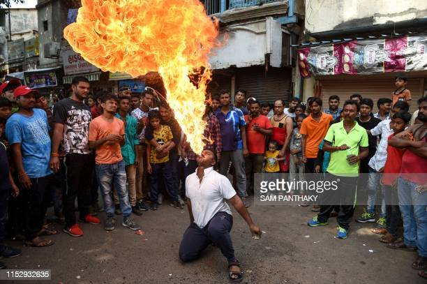 An Indian man Sunil Rana spits fire during the rehearsal for the forthcoming Lord Jagannath Rath Yatra an annual Hindi festival scheduled on July 4...