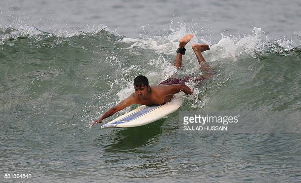 An Indian man surfs at Rushikonda Beach in Visakhapatnam on May 14 2016 / AFP / SAJJAD HUSSAIN