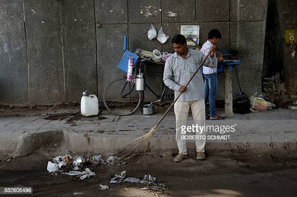 An Indian man sweeps a street in front of where Navin set up his older brother's bicycle food stand and was preparing a popular Indian dish called...