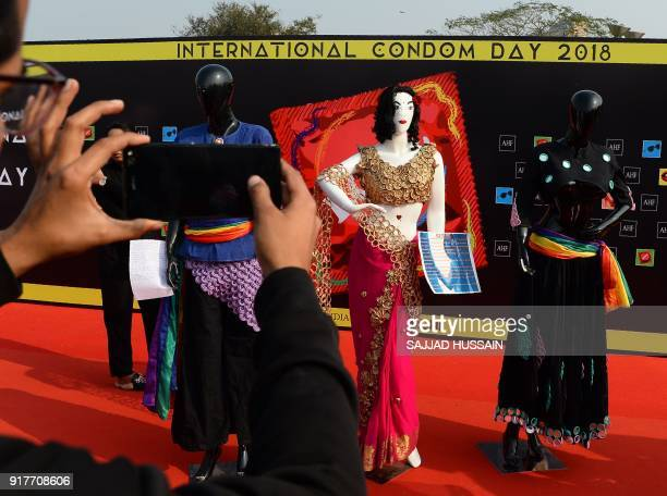 An Indian man take pictures from his mobile phone of a mannequin wearing a dress decorated with condoms during an event to mark International Condom...