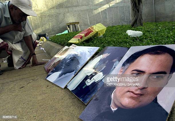 An Indian man takes a closer look at photographs of slain Indian prime minister Rajiv Gandhi on the eve of his 13th death anniversary in the Rajiv...