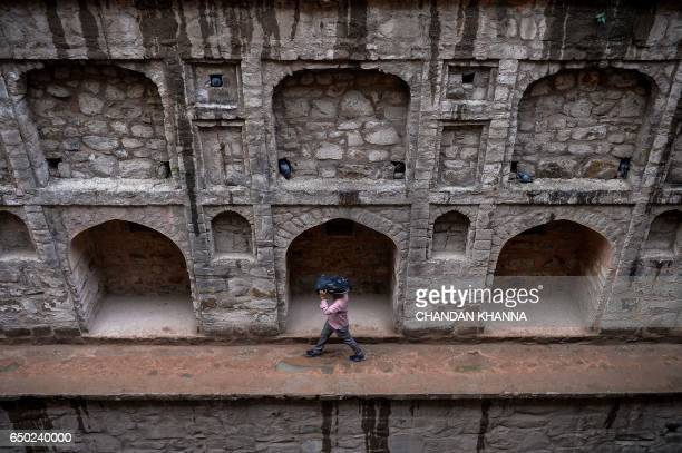 An Indian man takes covers his head with his bag as he walks inside the Agrasen ki Baoli during a rainfall in New Delhi on March 9, 2017. / AFP PHOTO...