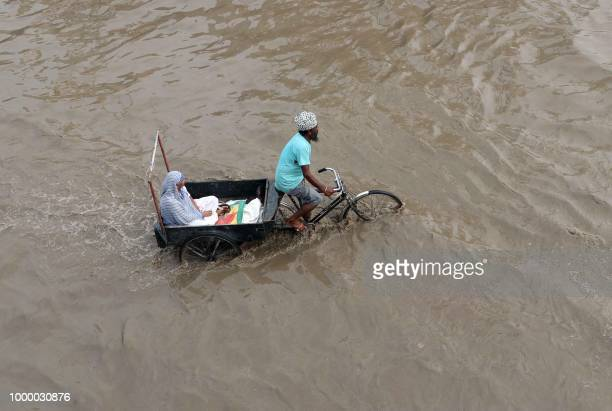 An Indian man transports a woman in the back of a cart connected to a bicycle as they make their way along a waterlogged road after heavy monsoon...