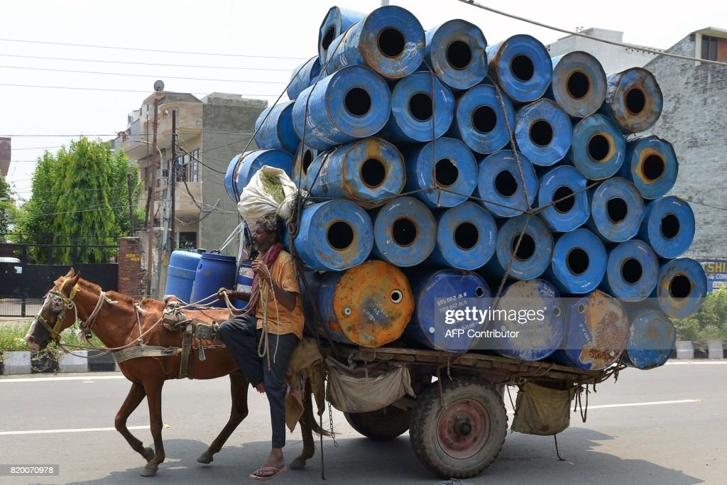 An Indian man transports empty container drums on a cart pulled by a horse in Amritsar on July 21 2017 / AFP PHOTO / NARINDER NANU