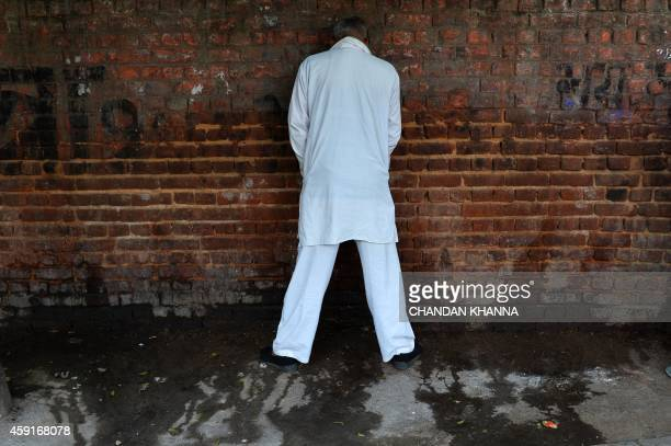 An Indian man urinates on a wall in New Delhi on November 18 the eve of World Toilet Day UNICEF estimates that almost 594 million or nearly 50...