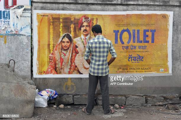 An Indian man urinates on a wall on the roadside in front of a poster for the Hindi film Toilet in Hyderabad on August 12 2017 The Bollywood film...