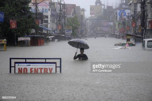 TOPSHOT An Indian man wades along a flooded street during a heavy downpour in Agartala the capital of northeastern state of Tripura on August 11 2017...