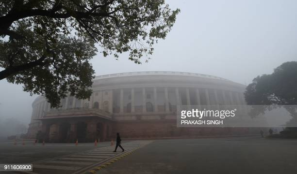An Indian man walk past the Parliament house prior to the begining of the budget session on a cold and foggy morning at in New Delhi on January 29,...