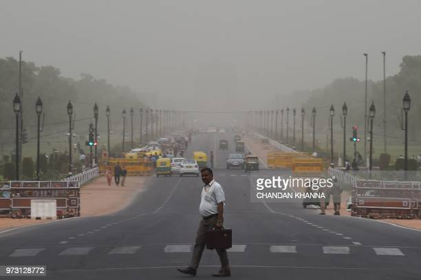 An Indian man walks across a road as the India Gate monument can be partially seen in the background during a period of duststorms in New Delhi on...