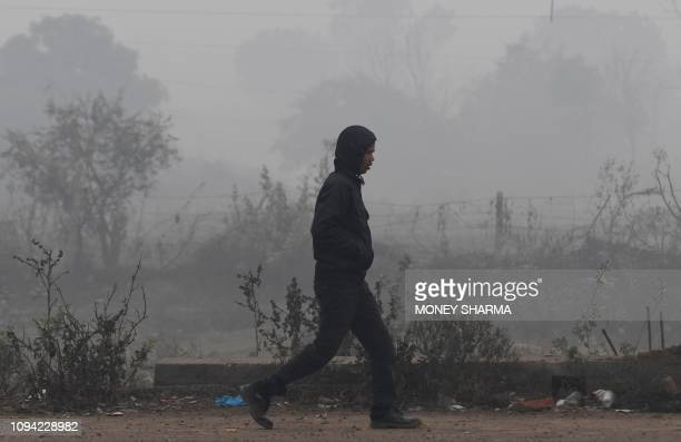 An Indian man walks along a path amidst smog and fog conditions during a cold morning in Faridabad on February 6, 2019. - Smog levels spike during...