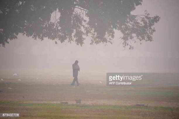An Indian man walks amid heavy smog near India Gate in New Delhi on November 13 2017 Schools reopened in New Delhi on November 13 despite a fresh...