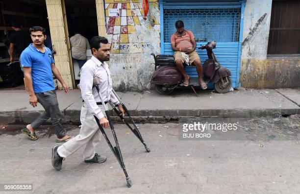 An Indian man walks on a road using crutches as a laborer rests on a scooter at a market in Guwahati on May 16 2018 Muslims throughout the world are...