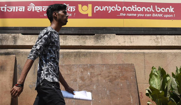 An Indian man walks past a sign for the stateowned Punjab National Bank in Mumbai on February 14 2018 India`s secondlargest staterun bank said...