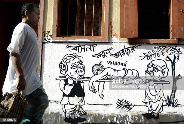 An Indian man walks past a wall adorned with a political cartoon a popular mode of election campaigning in Calcutta 13 April 2004 All the political...