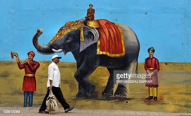 An Indian man walks past a wall mural depicting an elephant in Bangalore on July 21 2010 AFP PHOTO/Dibyangshu SARKAR