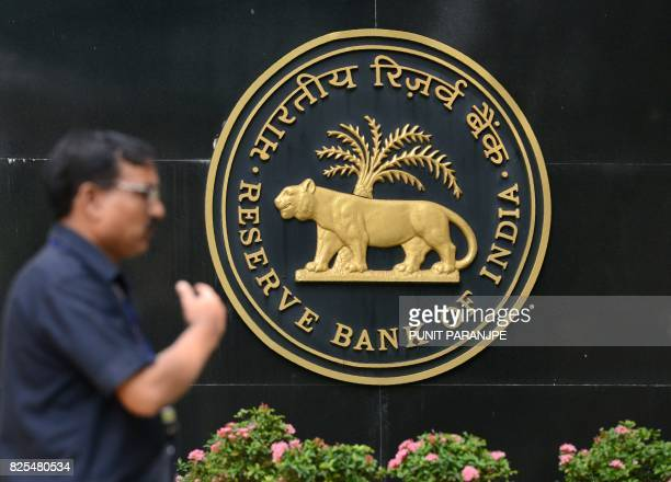 An Indian man walks past Reserve Bank of India logo at the headoffice in Mumbai on August 2 2017 India's central bank August 2 cut interest rates for...
