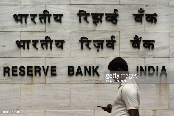 An Indian man walks past the entrance of the Reserve Bank of India head office in Mumbai on August 1 2018 India's central bank raised on August 1...