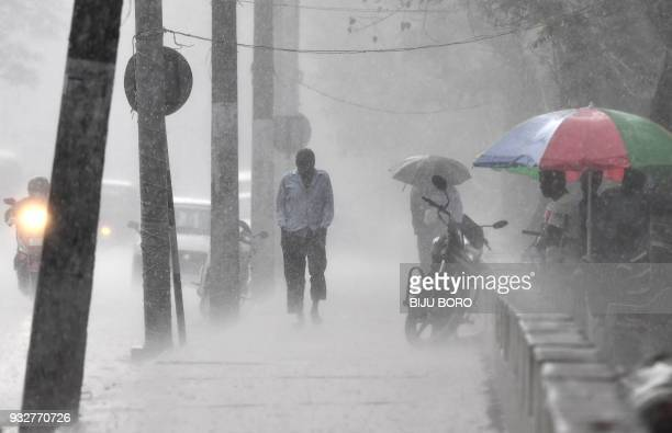 An Indian man walks through heavy rain along a street in Guwahati on March 16, 2018. / AFP PHOTO / Biju BORO