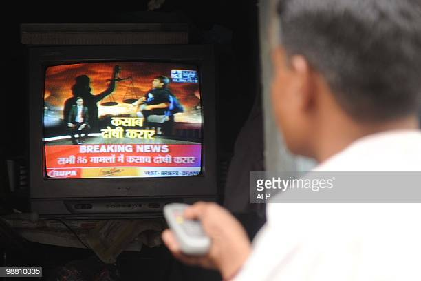An Indian man watches a television showing the Indian court verdict against alleged surviving gunman of the Mumbai massacre Mohammed Ajmal Amir Kasab...