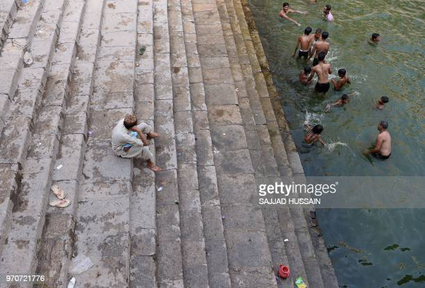 An Indian man watches as others cool off a 'baoli' or stepwell at the Nizamuddin Dargah in New Delhi on June 10 2018