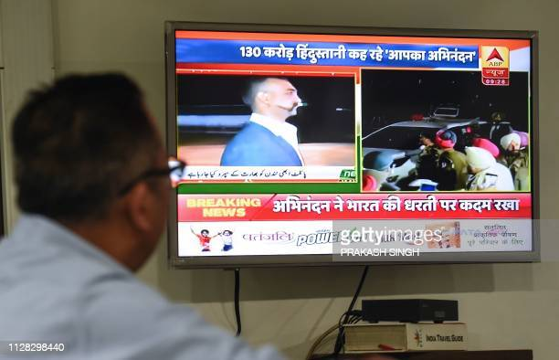 An Indian man watches live news channels broadcasting images of Indian Air Force Wing Commander pilot Abhinandan Varthaman returning to India from...