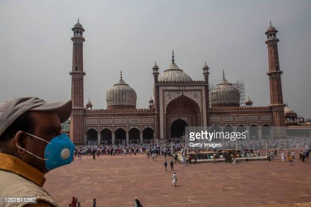 An Indian man wearing a protective mask as Muslims offer congregational Friday prayers at the historic Jama Masjid amid the government imposing...