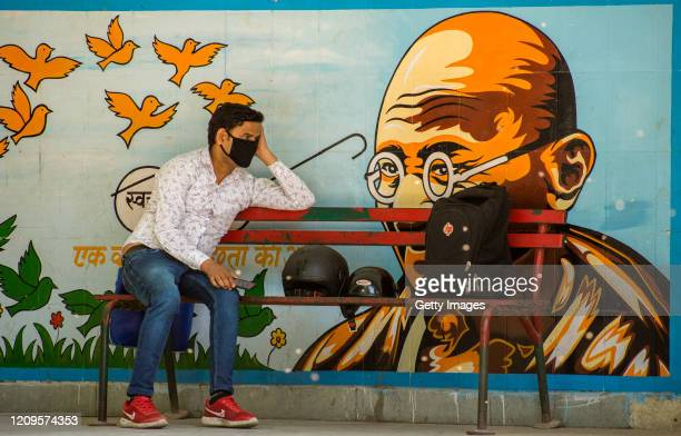 An Indian man wearing a protective mask sits on a bench, as India remains under an unprecedented lockdown over the highly contagious coronavirus on...