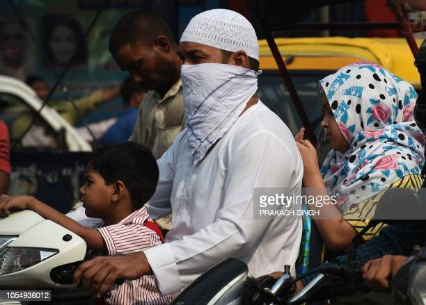 An Indian man wears a cloth on his face while waiting at a traffic junction in the old quarters of New Delhi on October 29 2018 Smog levels spike...