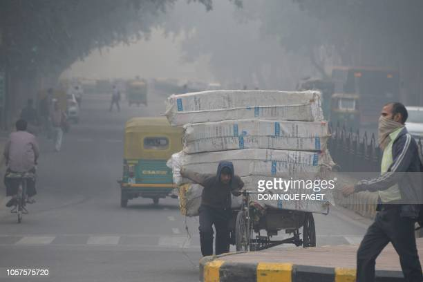 TOPSHOT An Indian man with his face covered walks amid heavy smog along a street in New Delhi on November 5 2018 Smog levels spike during winter in...