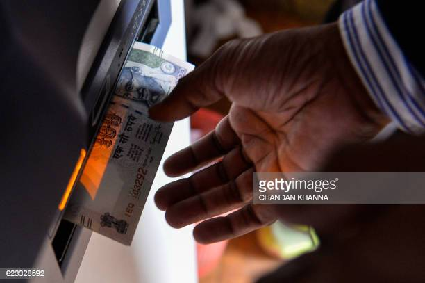 An Indian man withdraws money from a mobile bank ATM machine in New Delhi on November 15 2016 India is to use indelible ink to prevent people from...