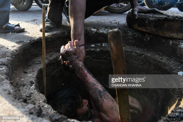 An Indian manual scavenger is helped out of a manhole in the old quarters of New Delhi on March 21 2018 Slum dwellers depend on government supplies...