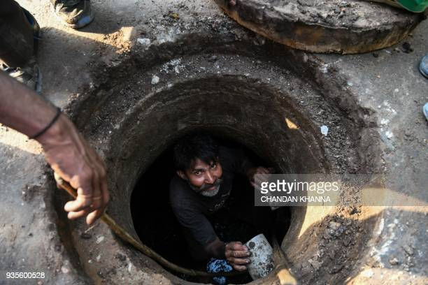 An Indian manual scavenger looks on as he cleans a manhole in the old quarters of New Delhi on March 21 2018 Slum dwellers depend on government...