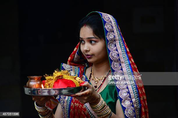 An Indian married Hindu woman performs rituals during the Karwa Chauth festival at Ram temple in Allahabad on October 11 2014 Karwa Chauth is a...
