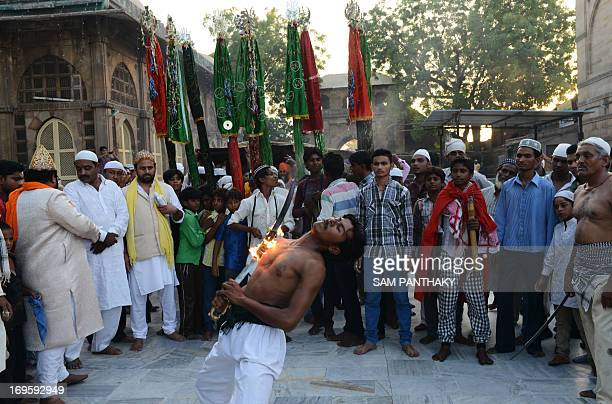 An Indian Mastan performs with a burning sword during a Rafai Silsila a religious procession to offer a ceremonial Chaddar at the ShahEAlam Roza in...