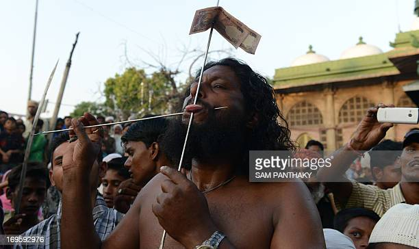 An Indian Mastan pierces his tongue and cheek during a Rafai Silsila a religious procession to offer a ceremonial Chaddar at the ShahEAlam Roza in...