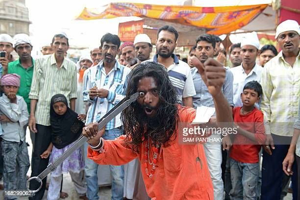 An Indian Mastan points a sword to his eyeball during a Rafai Silsila religious procession in memory of Qudri Rafai Junoon Ali Sai in Ahmedabad on...