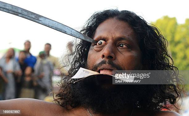 An Indian Mastan points a sword to his eyeball during a Rafai Silsila a religious procession to offer a ceremonial Chaddar at the ShahEAlam Roza in...