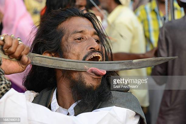 An Indian Mastan pushes a sword across is tongue during a Rafai Silsila religious procession in memory of Qudri Rafai Junoon Ali Sai in Ahmedabad on...