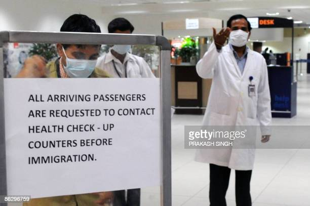 An Indian medical officer gestures as he asks air travellers to fill up health questionnaires upon arrival at the Indira gandhi International airport...
