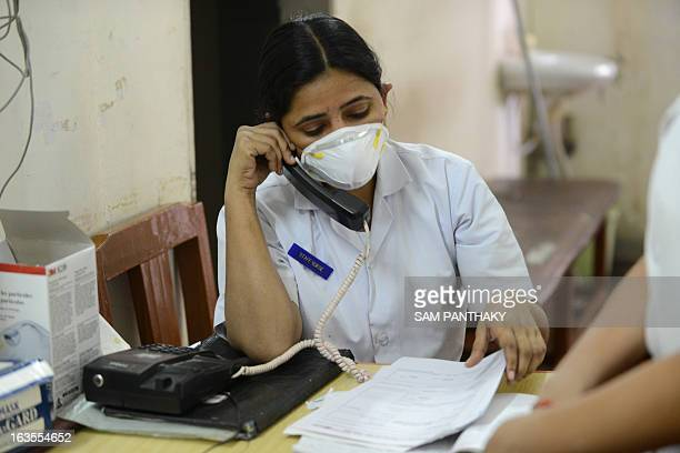 An Indian medical staff member talks on the phone outside an isolation ward for swine flu patients at the Ahmedabad Civil Hospital in Ahmedabad on...