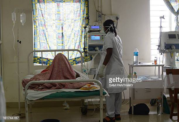 An Indian medical staff member treats a Swine Flu patients at an isolation ward of the Ahmedabad Civil Hospital in Ahmedabad on February 15 2013 In a...