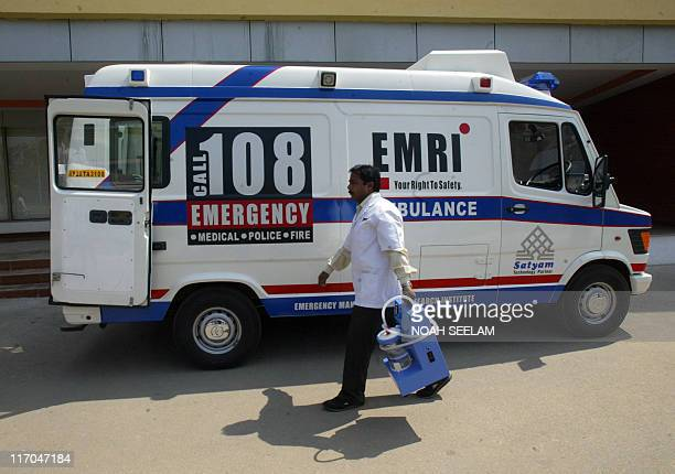 An Indian medical technician walks past an Emergency Management and Research Institute ambulance in Hyderabadon February 18 2009 EMRI is the only...