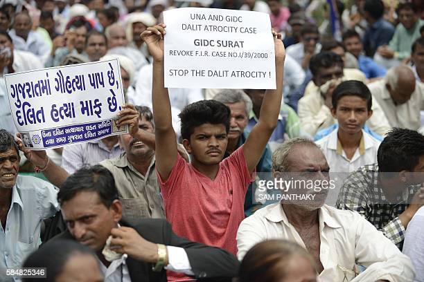 An Indian member of the Dalit caste community holds a placard saying 'In Gujarat Cow Slaughter is a Sin while Killing Dalits is pardonable' as he...