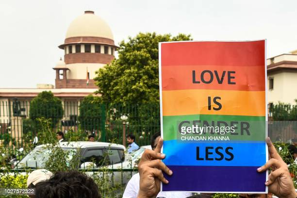 An Indian member of the lesbian gay bisexual transgender community holds a placard outside the Supreme Court after the decision to strike down the...