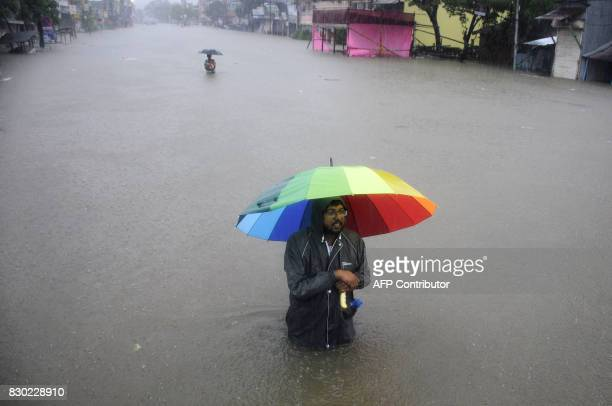 An Indian men wade while holding an umbrella through a flooded street during a heavy downpour in Agartala the capital of northeastern state of...