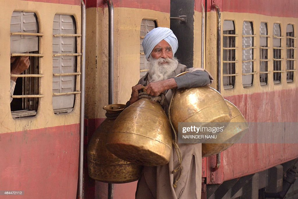 An Indian milkman carries milk containers as he boards a train at a railway station in Amritsar on February 26 2015 India said it would spend 137...